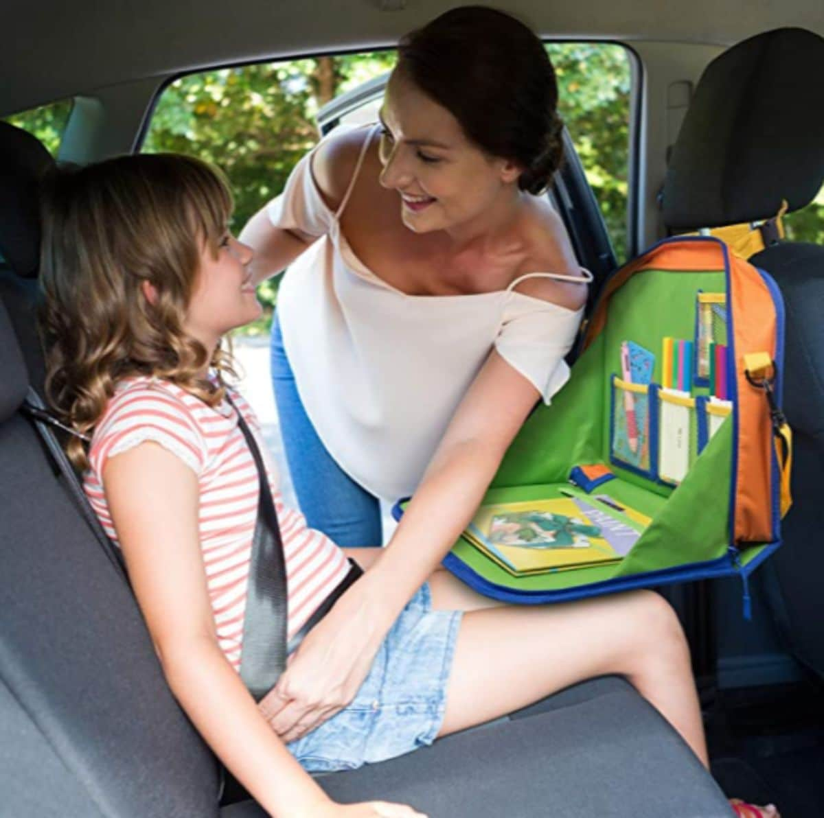 A mom fixes her child's seatbelt. The child is sitting behind an activity center attached to the seat in front of her