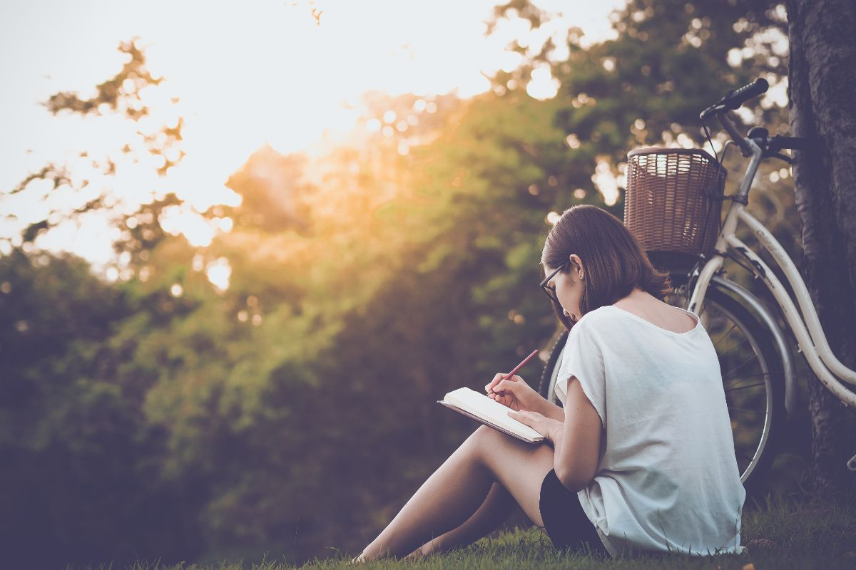 a white girl sits on the grass next to a bicycle as the sun sets, writing in a book