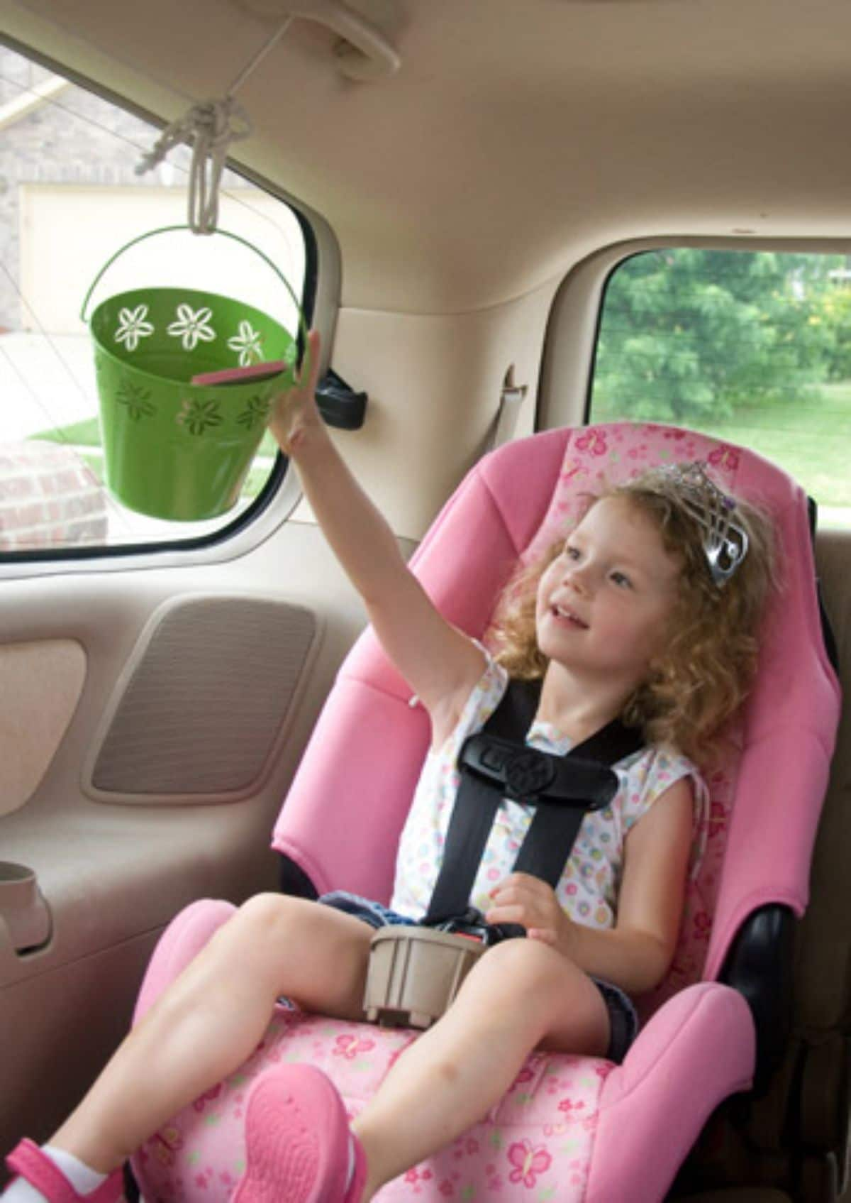 a girl in a pink car seat reaches up towards a green bucket hanging from a string