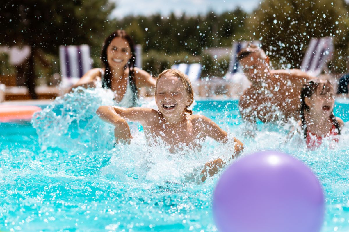2 children and 2 adults splash in a pool with a purple beach ball
