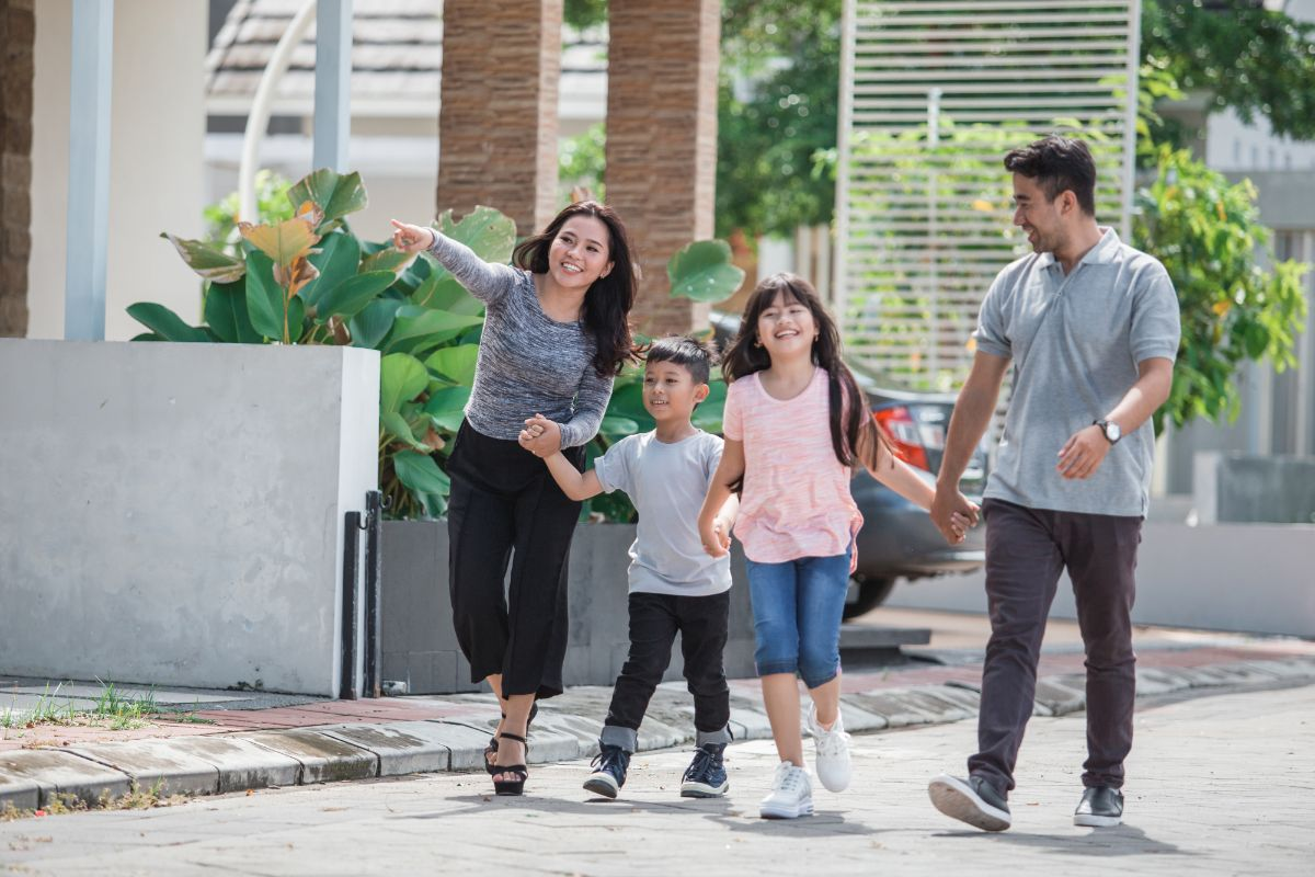 an asian family hold hands and walk down a street
