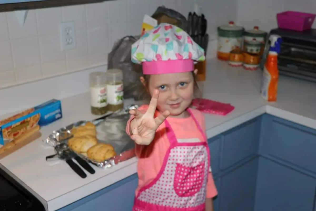a girl in a pink chefs hat and apron looks at the camera and holds up the peace sign