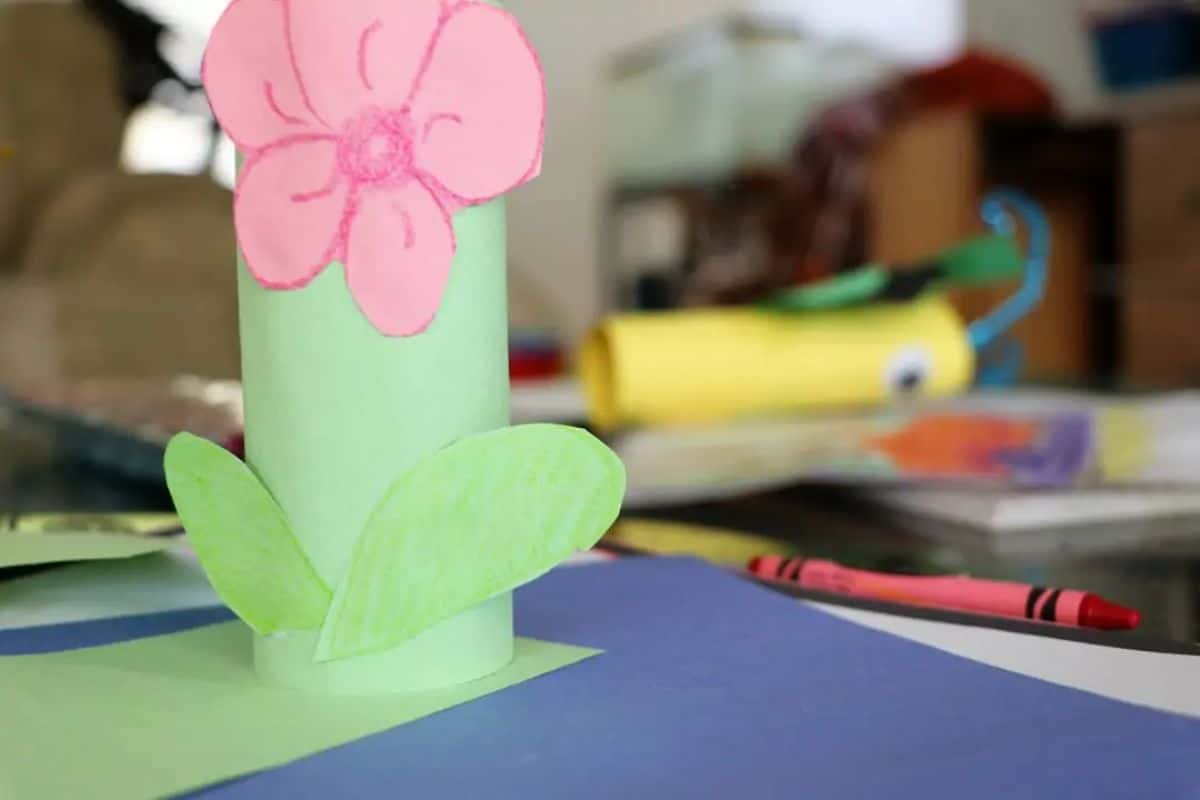 a close up of a table full of craft materials. A flower has been made out of toilet roll and paper