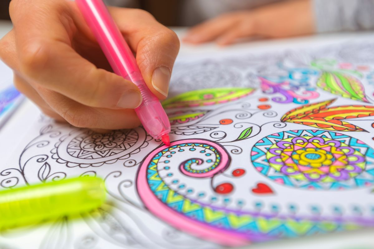 a hand holds a pink pen and colors in a detailed design