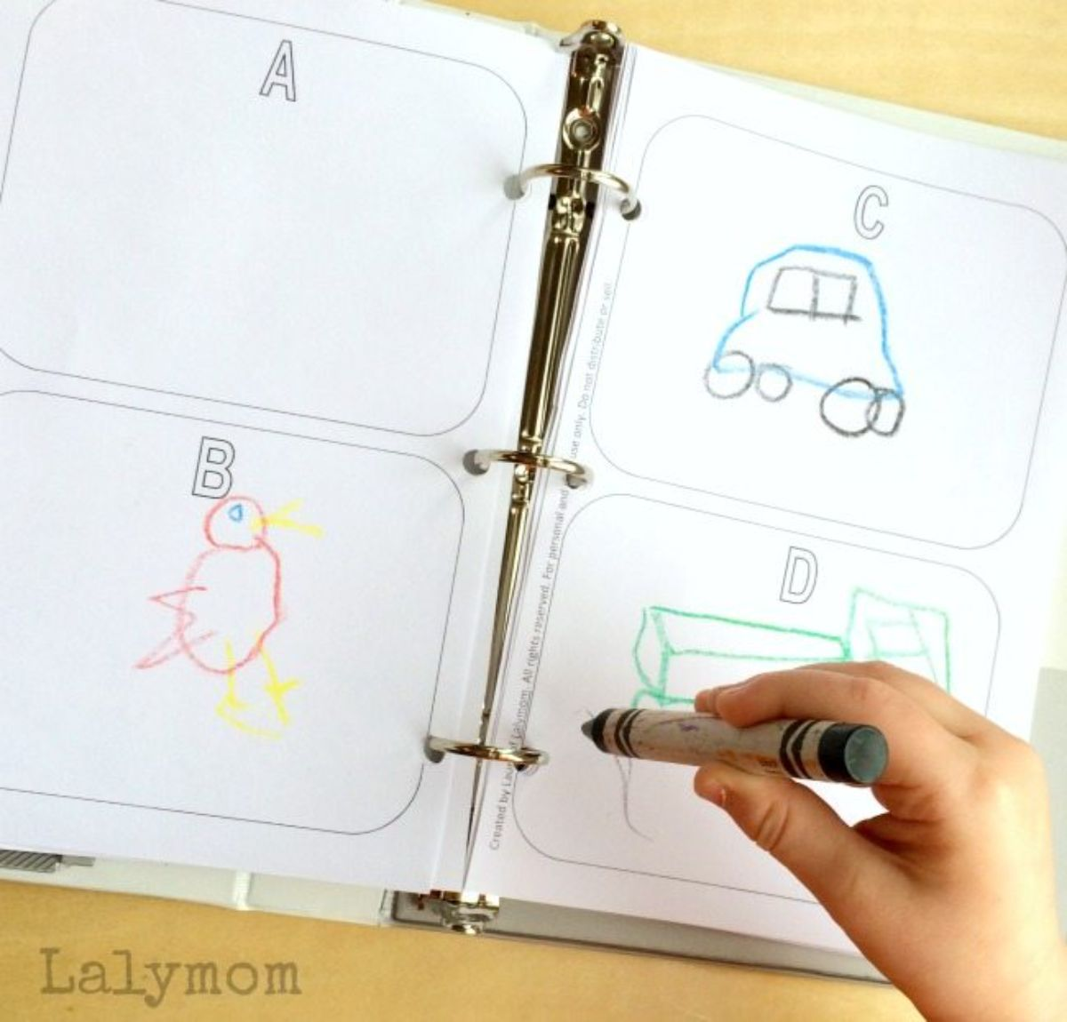 a hand holds a green crayon towards a ring binder with paper in it. Each sheet has 4 squares labelled A-D with pictures drawn on it