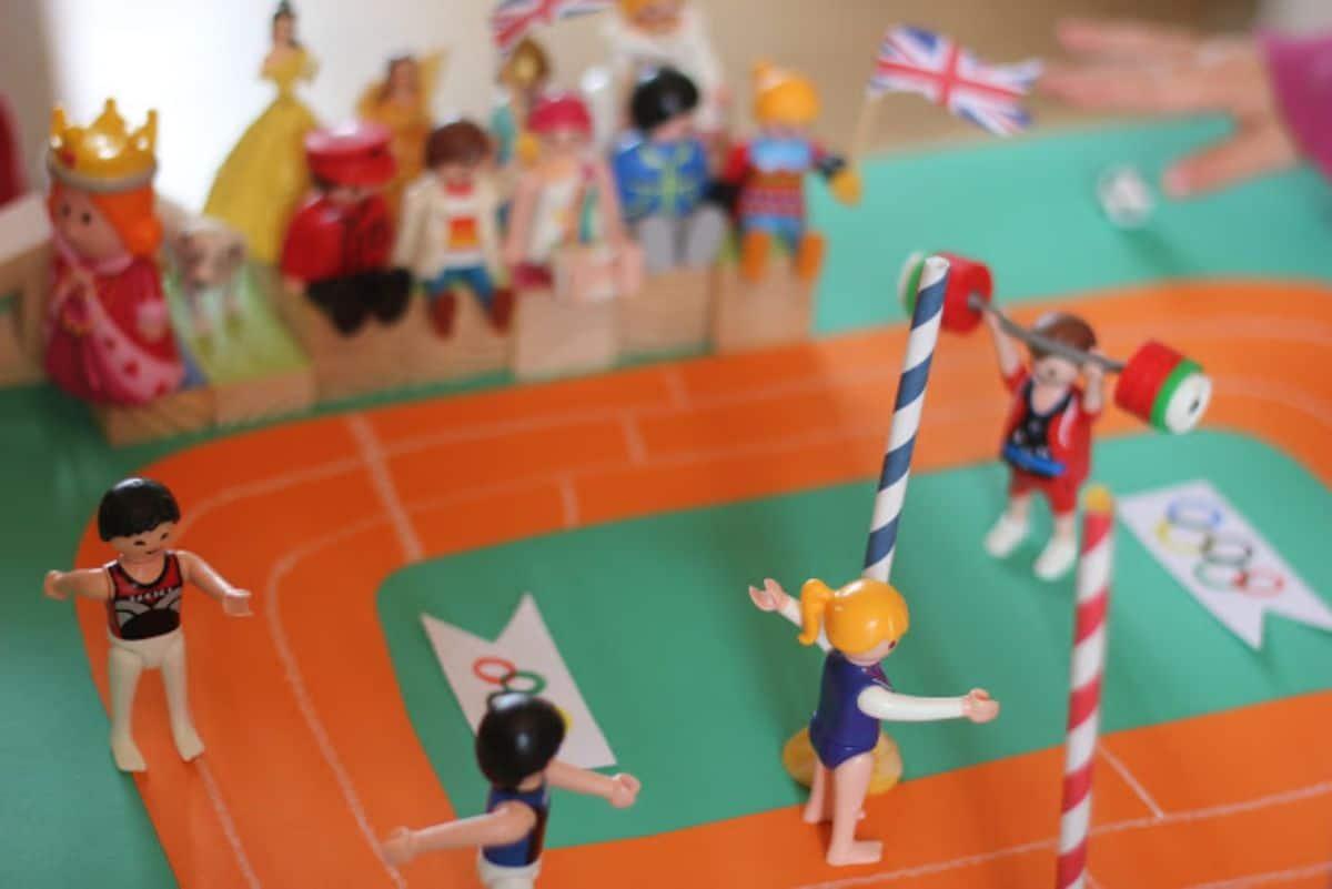 playmobil figures run around a paper athletics track