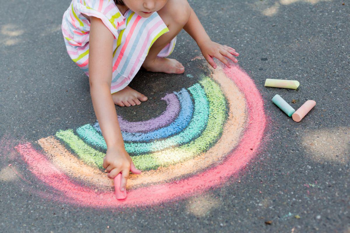 a girl in a rainbow dress colors a rainbow on the sidewalk in chalk