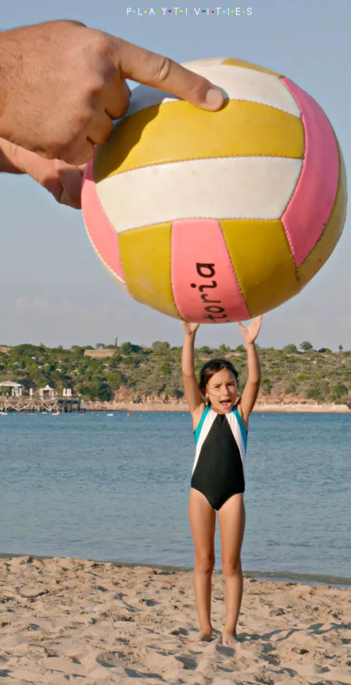 a girl in a black swimsuit raches up as if to hold agiant beachball over her haed. The ball is being held by two large hands. The backdrop is a beach