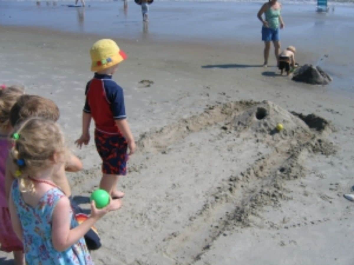 children stand on a beach with a skee ball track made of sand in front of them