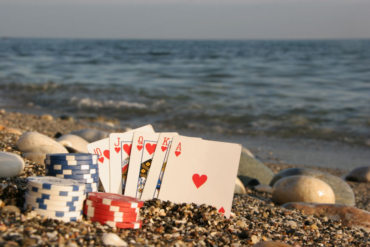 playing cards and poker chips are dug into shingle on a beach