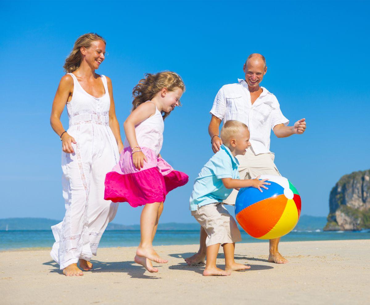 a mom, dad, girl and boy play with a beach ball on a sunny beach