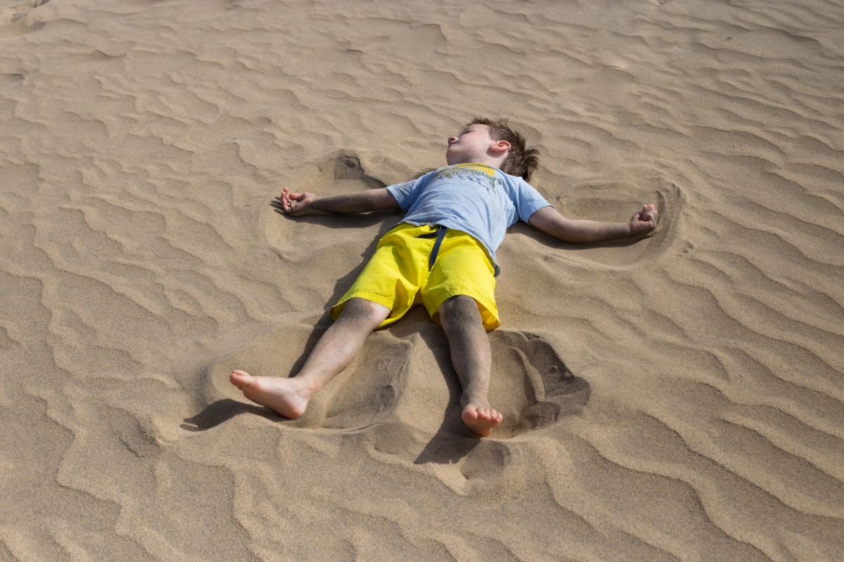 a dark haired boy lays in the sand wearing a blue tshirt and yellow shorts