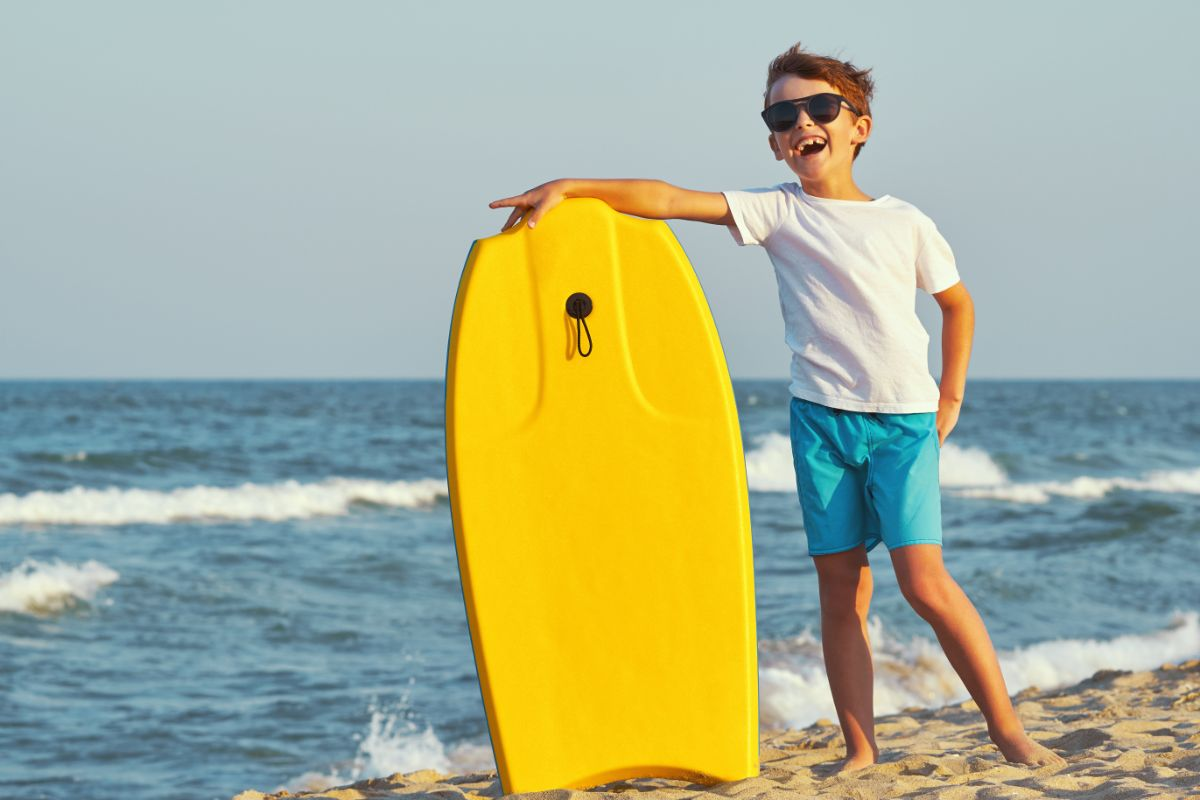 a dark haired boy in sunglasses, blue shorts and a white tshirt holds a yellow boogie board on a beach