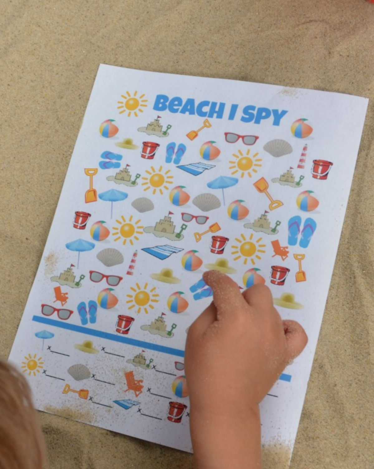 a hand points at a beach ispy sheet on the sand