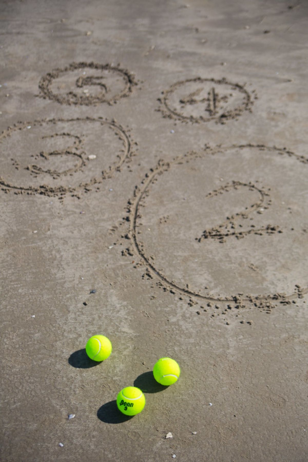 3 tennis balls sit on sand in front of the numbers 5, 4, 3, and 2 drawn circled in the sand
