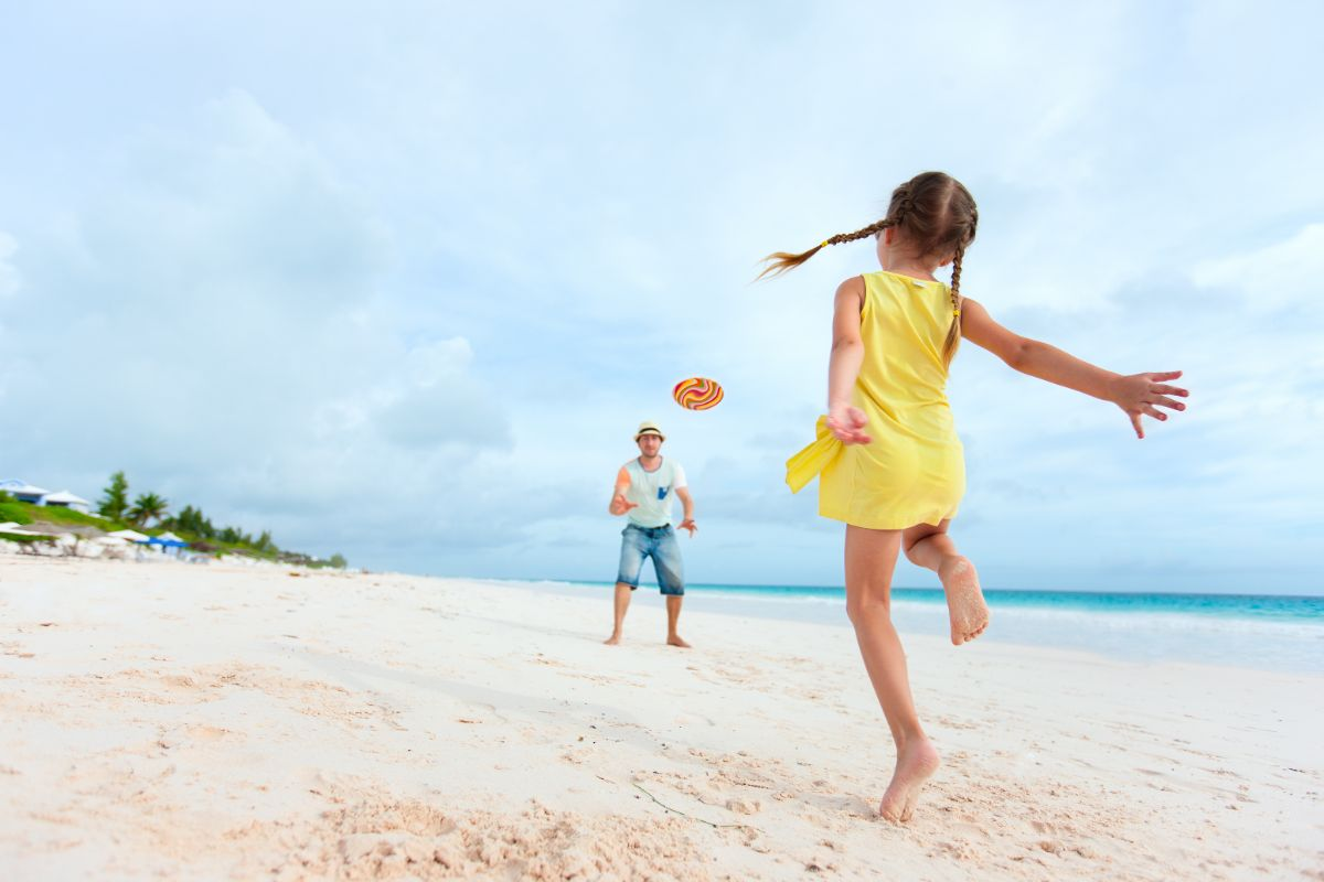 a girl in a yellow dress and a man in blue play frisbee on a beach