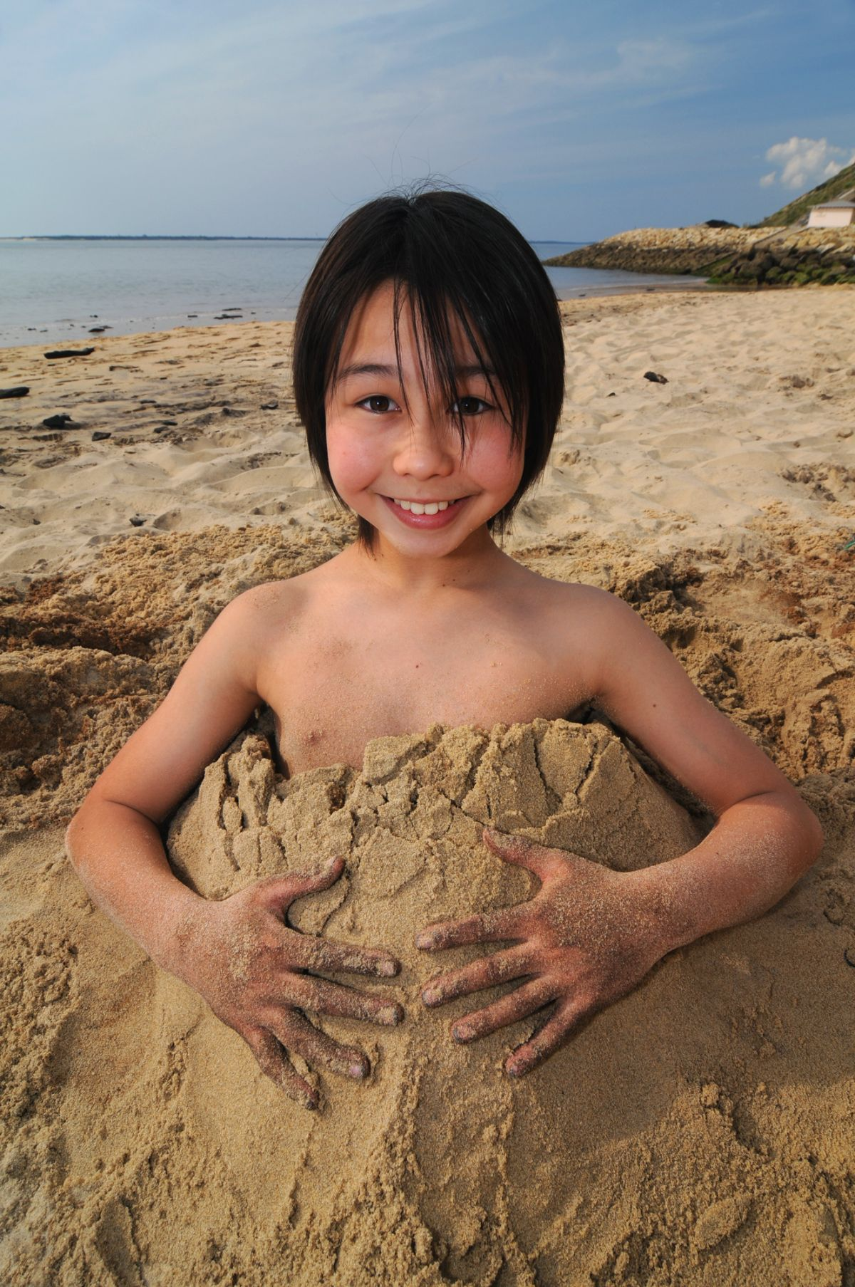 a boy with dark hair smiles at the camera buried up to his chest in sand
