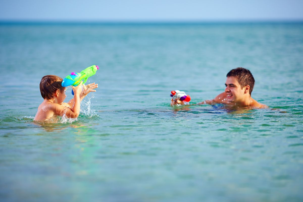 a boy and man stand shoulder-deep in the sea pointing super soakers at each other