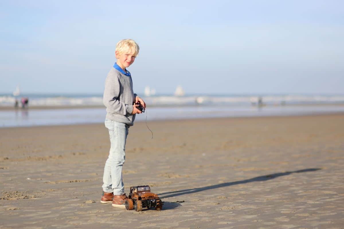 a blonde boy in grey clothes stands on a beach holding a remote control. A remote control car drives away from him