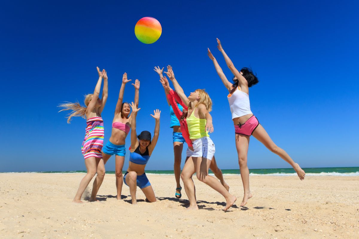 a group of children in summer clothes play with a beach ball on a sunny beach