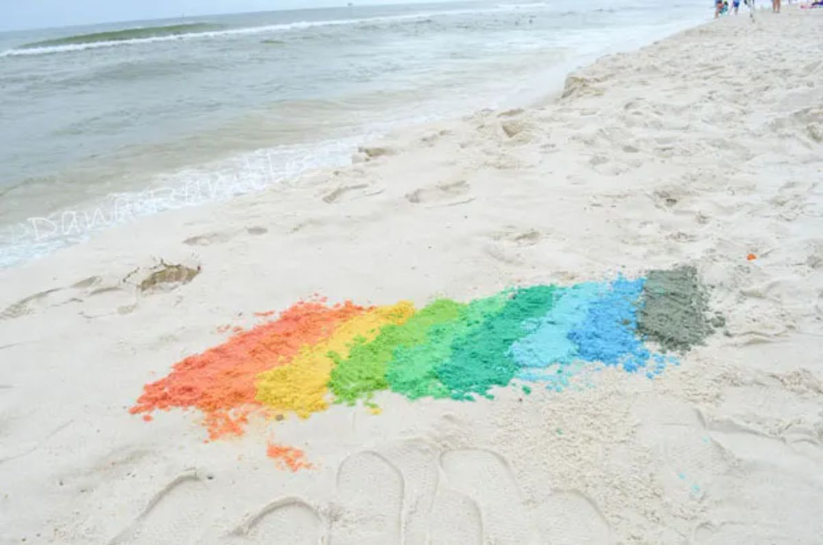 a rainbow of colored sand sits on the beach with sea in the background