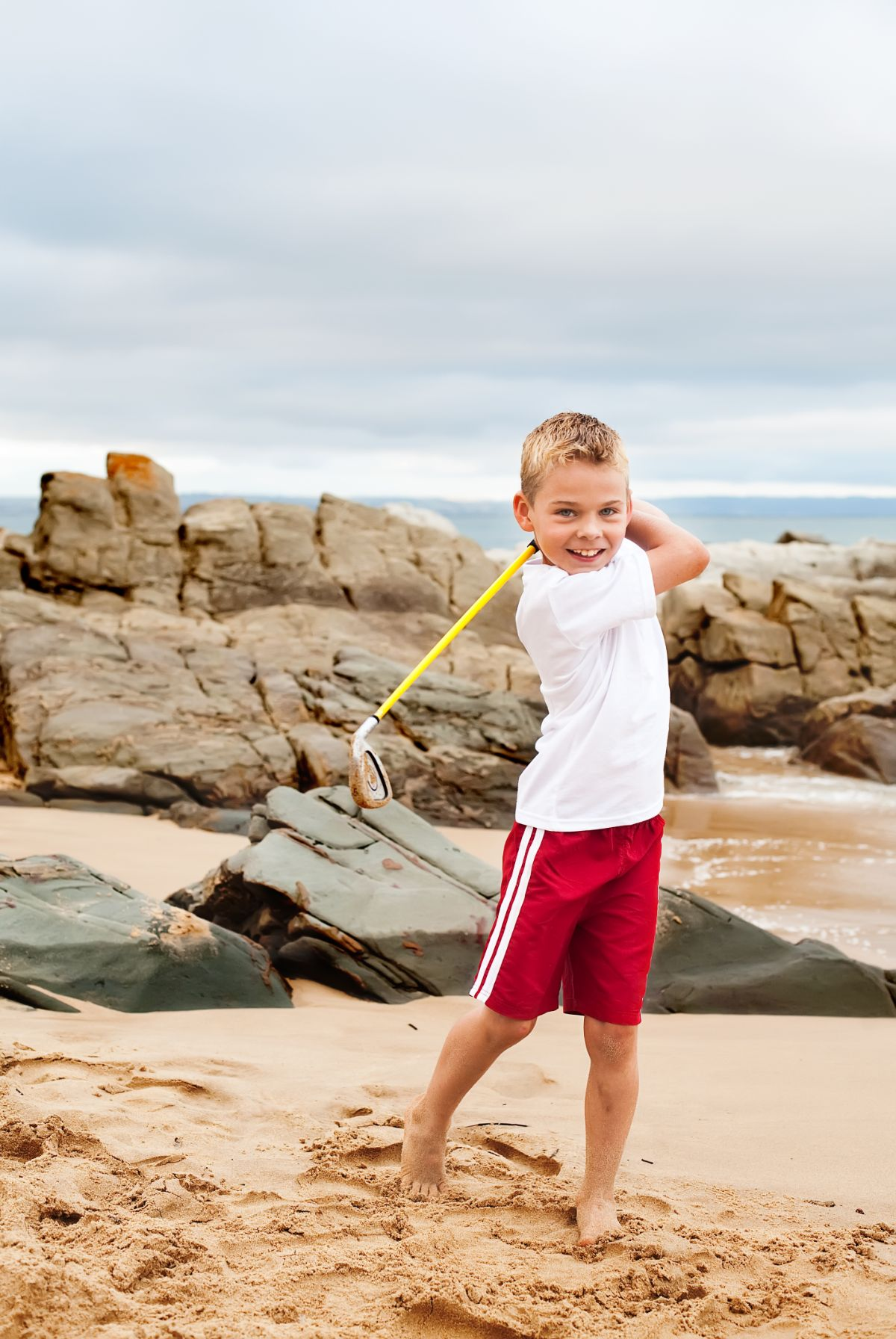 a boy in white tshirt and red shorts swings a yellow golf club behind him, standing in front of rocks