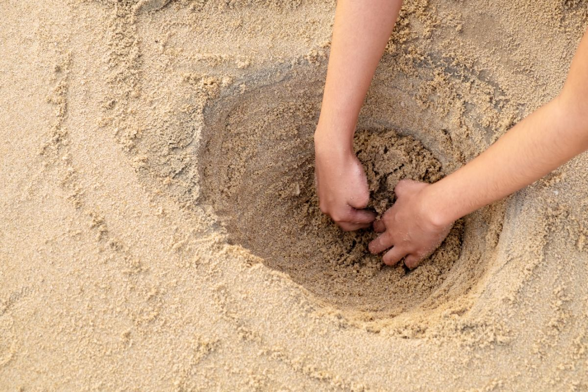 two hands dig a hole in the sand