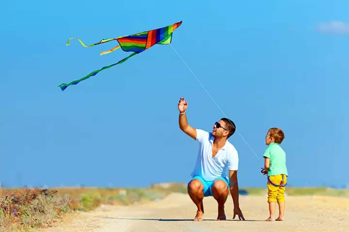 a man and young boy fly a kite on a sunny beach