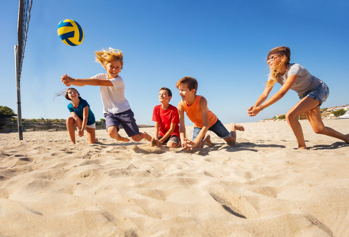 a group of children play beach volleyball