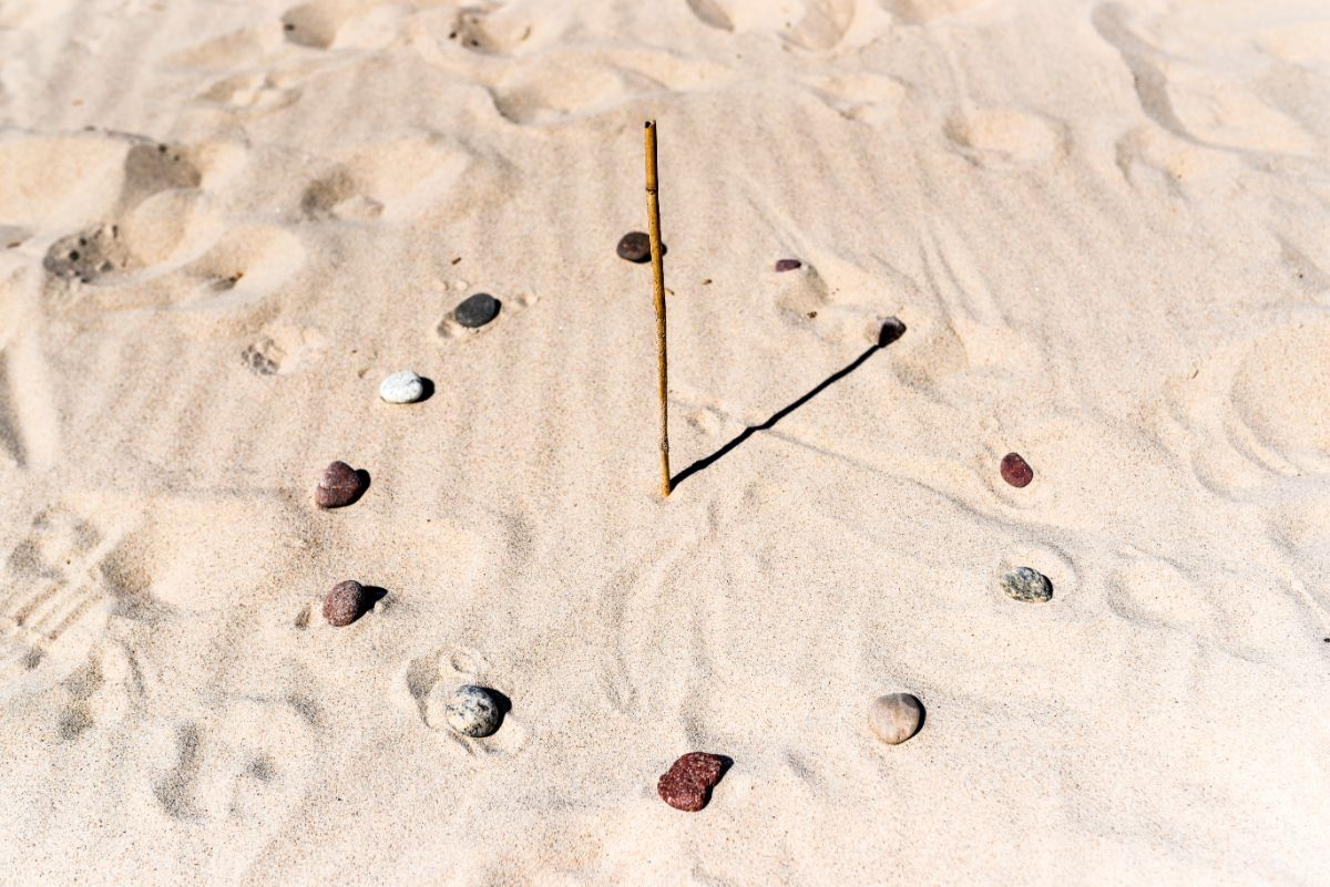 a sundial made out of stones and a stick in the sand
